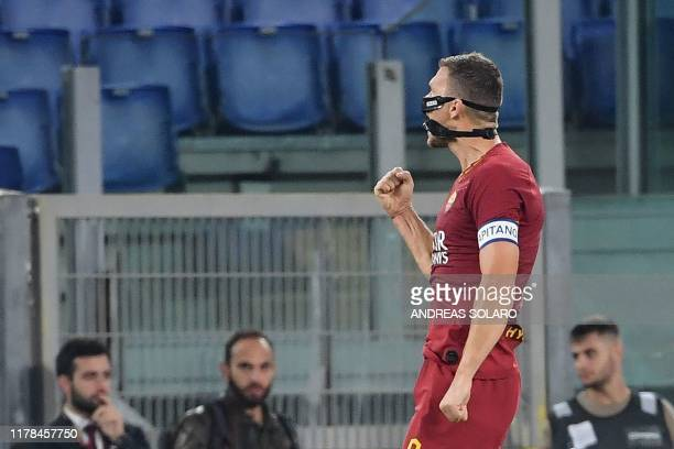 AS Roma's Bosnian forward Edin Dzeko celebrates after scoring a goal during the Italian Serie A football match between AS Roma and AC Milan on...