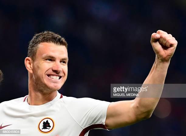 AS Roma's Bosnian forward Edin Dzeko celebrates after scoring during the Italian Serie A football match AC Milan vs AS Roma at the San Siro stadium...