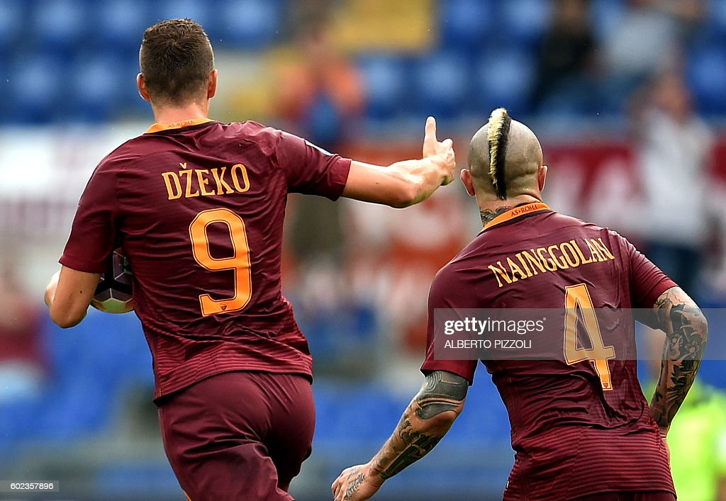 AS Roma's Bosnian forward Edin Dzeko (L) celebrates next to AS Roma's Belgian midfielder Radja Nainggolan (R) after scoring a goal during the Italian Serie A football match between AS Roma and Sampdoria on September 11, 2016 at the Olympic stadium in Rome. / AFP / ALBERTO