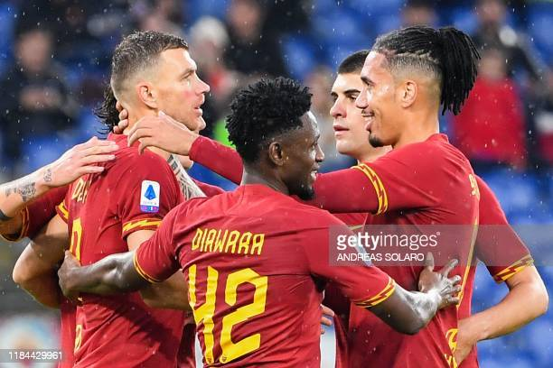 AS Roma's Bosnian forward Edin Dzeko celebrates with teammates after scoring during the Italian Serie A football match Roma vs Brescia on November 24...