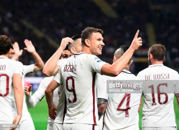 AS Roma's Bosnian forward Edin Dzeko celebrates with teammates after scoring during the Italian Serie A football match AC Milan vs AS Roma at the San...
