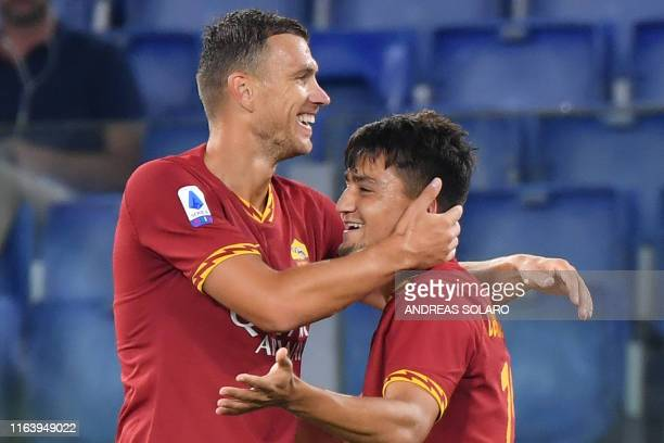 Roma's Bosnian forward Edin Dzeko congratulates AS Roma's Turkish forward Cengiz Under after he opened the scoring during the Italian Serie A...