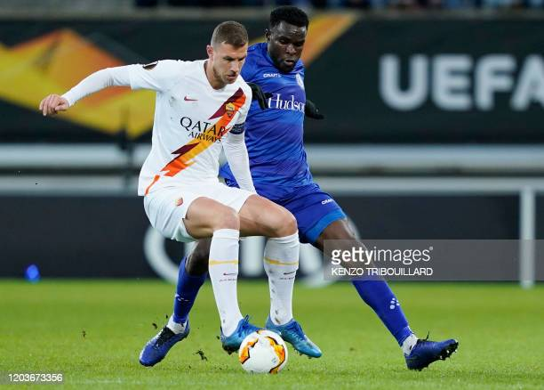AS Roma's Bosnian forward Edin Dzeko is challenged by Ghent's Cameroon defender Michael NgadeuNgadjui during the UEFA Europa League round of 32...