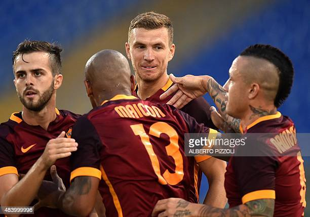 Roma's Bosnian forward Edin Dzeko is congratulated by teammates after scoring goal during the friendly football match AS Roma vs Sevilla on August 14...
