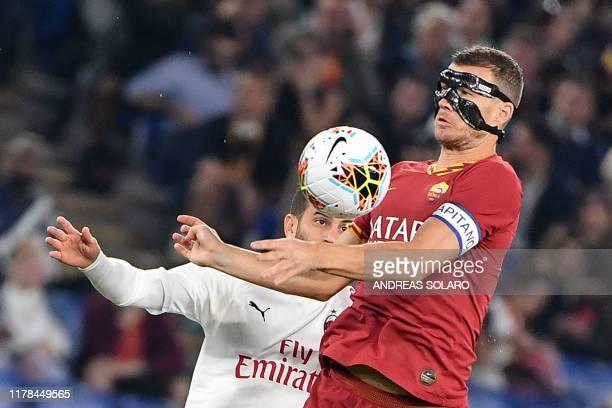 AS Roma's Bosnian forward Edin Dzeko jumps for the ball with AC Milan's Italian defender Mateo Musacchio during the Italian Serie A football match...