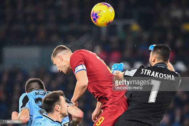 Roma's Bosnian forward Edin Dzeko jumps to open the scoring past Lazio's Albanian goalkeeper Thomas Strakosha during the Italian Serie A football...