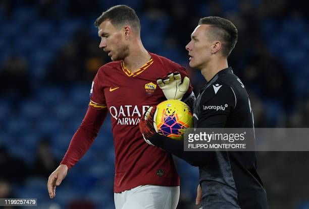 AS Roma's Bosnian forward Edin Dzeko reacts with Bologna's Polish goalkeeper Lukasz Skorupski during the Italian Serie A football match between AS...