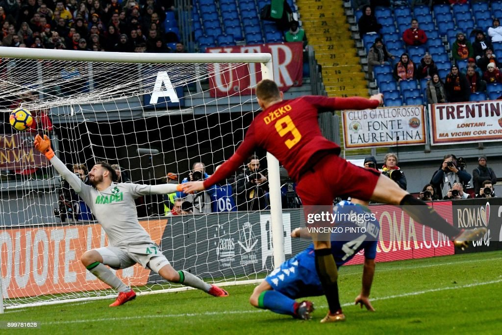 AS Roma's Bosnian forward Edin Dzeko (C) scores a goal later to be found invalid during the Italian Serie A football match AS Roma versus Sassuolo on December 30, 2017 at the Olympic stadium in Rome. / AFP PHOTO / Vincenzo PINTO