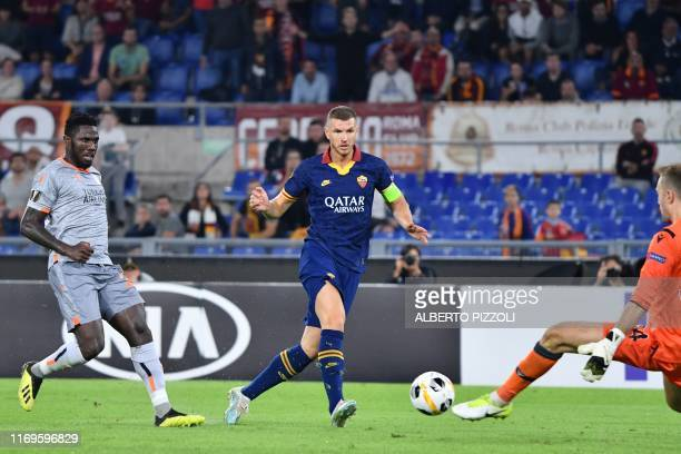 Roma's Bosnian forward Edin Dzeko shoots on goal as Istanbul Basaksehir FK's Turkish goalkeeper Mert Gunok defends and Istanbul Basaksehir FK's Cape...