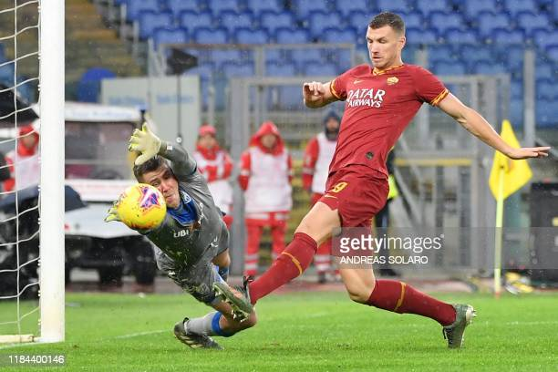 Roma's Bosnian forward Edin Dzeko shoots to score his team's third goal past Brescia's Finnish goalkeeper Jesse Joronen during the Italian Serie A...