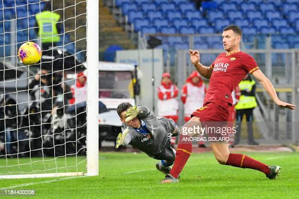 AS Roma's Bosnian forward Edin Dzeko shoots to score his team's third goal past Brescia's Finnish goalkeeper Jesse Joronen during the Italian Serie A...
