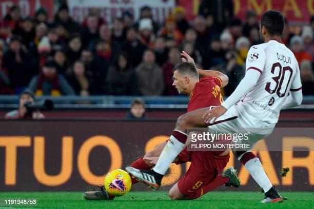 Roma's Bosnian forward Edin Dzeko vies for the ball with Torino Ivorian defender Koffi Djidji during the Italian Serie A football match between Roma...