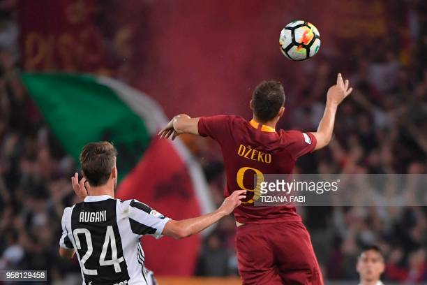 Roma's Bosnian striker Edin Dzeko and Juventus' defender from Italy Daniele Rugani jump for the ball during the Italian Serie A football match AS...