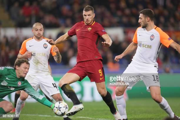 Roma's Bosnian striker Edin Dzeko attempt to score as FC Shakhtar's Ukrainian goalkeeper Andrij Pyatov keep the ball next to FC Shakhtar's Ukrainian...