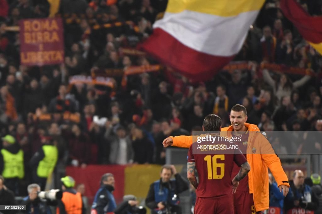 Roma's Bosnian striker Edin Dzeko celebrates (R) with Roma's Italian midfielder Daniele De Rossi afer winning 1-0 the UEFA Champions League round of 16 second leg football match AS Roma vs Shakhtar Donetsk on March 13, 2018 at the Olympic stadium in Rome. Roma reached the Champions League quarter-finals for the first time in 10 years as Edin Dzeko edged them past Shakhtar Donetsk 1-0 at the Stadio Olimpico on Tuesday for an away goals victory. / AFP PHOTO / Andreas SOLARO