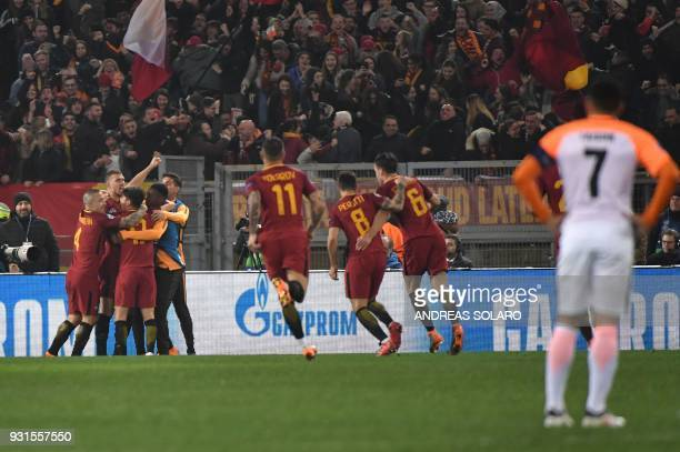 TOPSHOT Roma's Bosnian striker Edin Dzeko celebrates with teammates after scoring during the UEFA Champions League round of 16 second leg football...