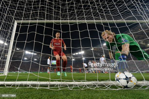 Roma's Bosnian striker Edin Dzeko enters the goal as Liverpool's German goalkeeper Loris Karius picks up the ball after a Liverpool's own goal during...