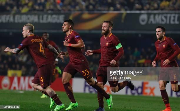 Roma's Brazilian defender Emerson Palmieri celebrates a goal with Roma's midfielder Daniele de Rossi Roma's Dutch midfielder Kevin Strootman and...