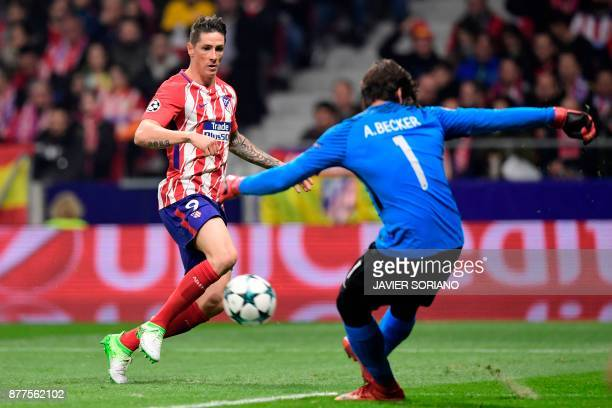 Roma's Brazilian goalkeeper Alisson stops a shot on goal by Atletico Madrid's Spanish forward Fernando Torres during the UEFA Champions League group...
