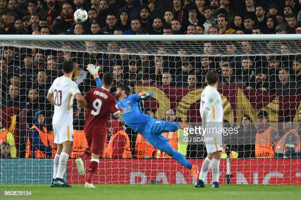 Roma's Brazilian goalkeeper Alisson stretches and fails to stop Liverpool's first goal during the UEFA Champions League first leg semifinal football...