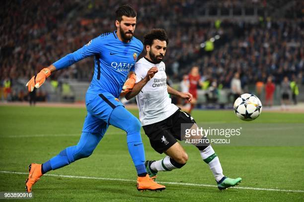Roma's Brazilian goalkeeper Alisson vies with Liverpool's Egyptian midfielder Mohamed Salah during the UEFA Champions League semifinal second leg...