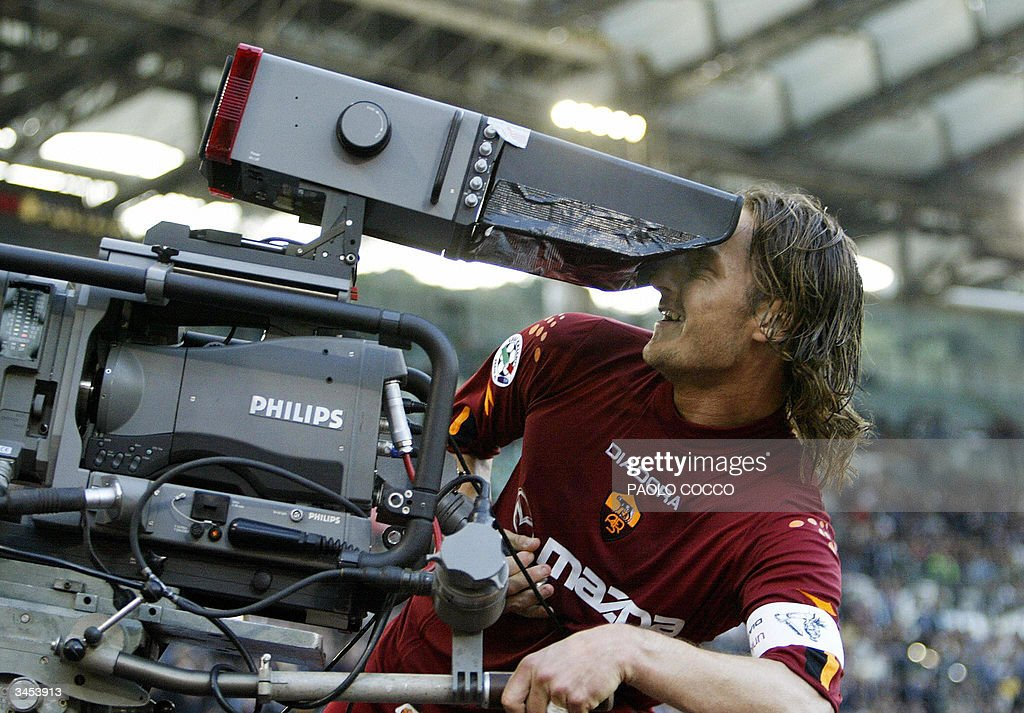 AS Roma's captain Francesco Totti celebrates with a tv camera after scoring against Lazio during their Serie A soccer match at Rome's Olympic stadium 21 April 2004.