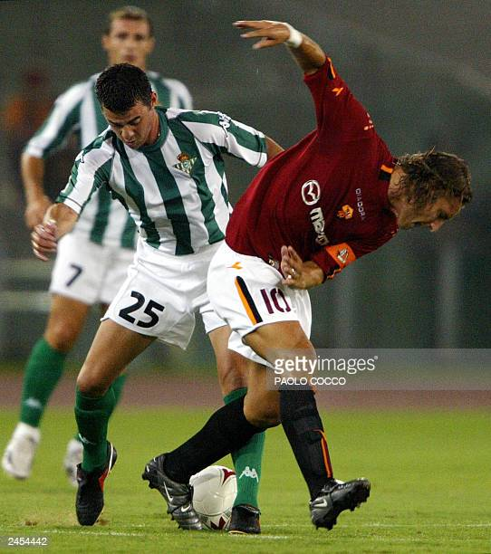 AS Roma's captain Francesco Totti is tackled by Real Betis player Arturo Garcia Munoz as teammate Fernando Varela Ramos looks on during their...