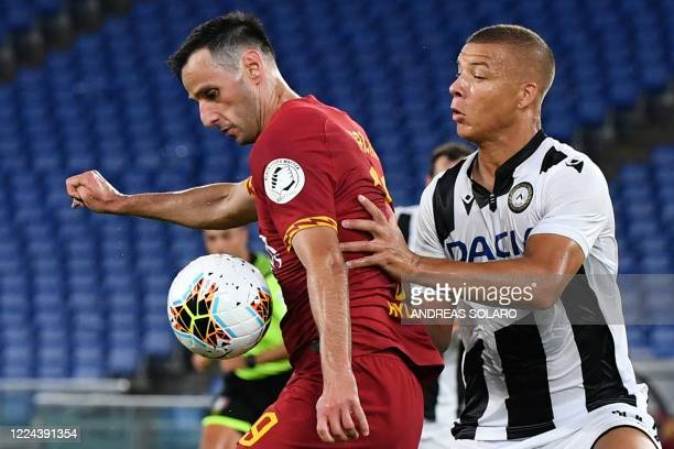 Roma's Croatian forward Nikola Kalinic holds off Udinese's French defender Sebastien De Maio during the Italian Serie A football match Roma vs...