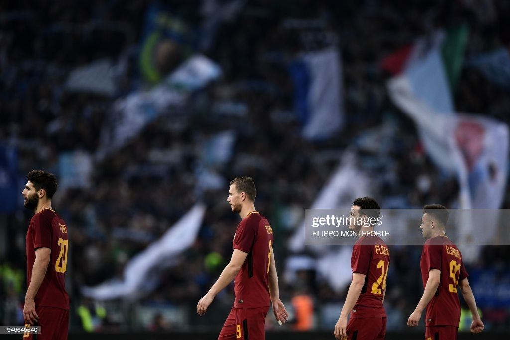 Roma's defender from Argentina Federico Fazio, forward from Bosnia and Herzegovina Edin Dzeko, midfielder Alessandro Fiorenzi and forward Stephan El Shaarawy leave the pitch at the end of the Italian Serie A football match Lazio vs Roma at the Olympic Stadium in Rome on April 15, 2018. /