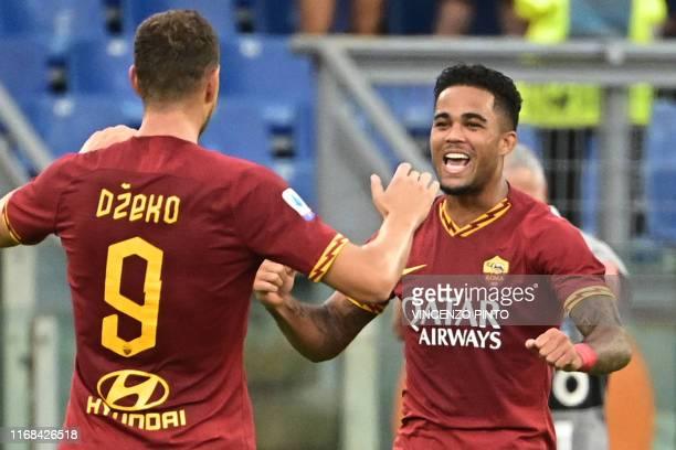 Roma's Dutch forward Justin Kluivert celebrates with AS Roma's Bosnian forward Edin Dzeko after scoring his team's fourth goal during the Italian...