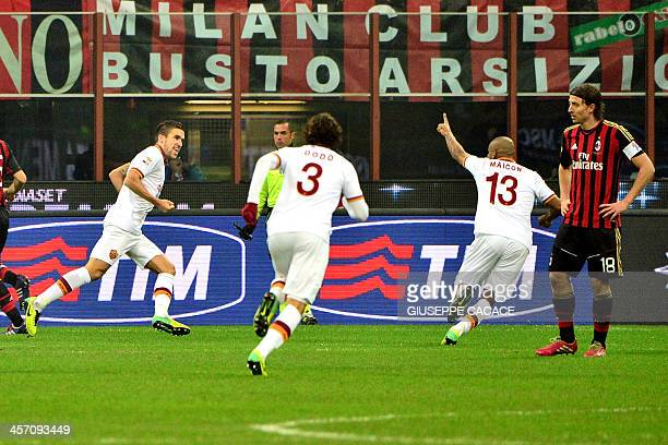 AS Roma's Dutch forward Kevin Strootman celebrates with teammates after scoring a penalty during the Serie A football match between AC Milan and Roma...