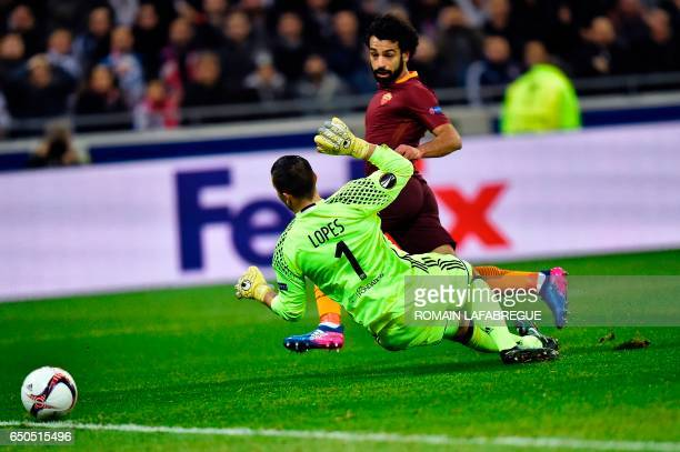 Romas Egyptian midfielder Mohammed Salah shoots and scores past Lyon's French goalkeeper Anthony Lopes during the Europa League round of 16 first leg...