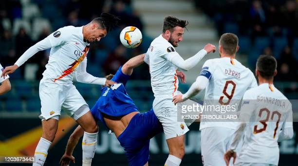 AS Roma's English defender Chris Smalling heads the ball with Ghent's Belgian forward Laurent Depoitre and AS Roma's Italian midfielder Bryan...