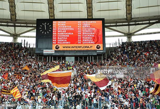 AS Roma's fans cheer as the scoreboard shows their team only one point behind InterMilan after today' win against Atalanta in Serie A football match...