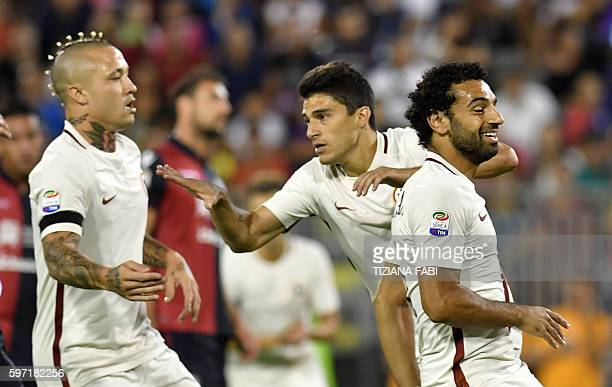 Roma's forward Diego Perrotti celebrates with teammates after scoring a goal during the Serie A football match between Cagliari and Roma at the...