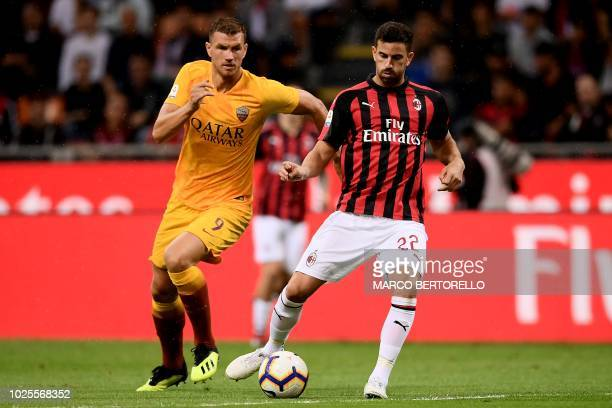 AS Roma's forward Edin Dzeko from BosniaHerzegovina fights for the ball with AC Milan's defender Mateo Musacchio from Argentina during the Italian...