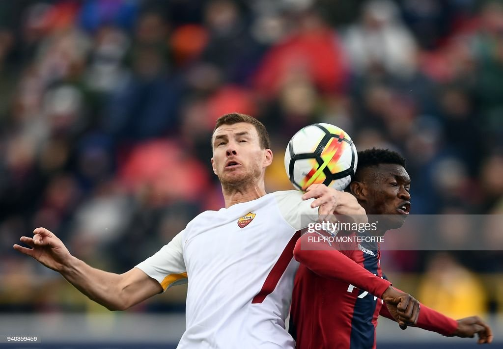 Roma's forward from Bosnia ed Erzegovina Edin Dzeko (L) heads the ball next to Bologna's defender from Senegal brahima Mbaye during the Italian Serie A football match Bologna vs AS Roma at the Renato D'all'Ara Stadium in Bologna, on March 31, 2018. /