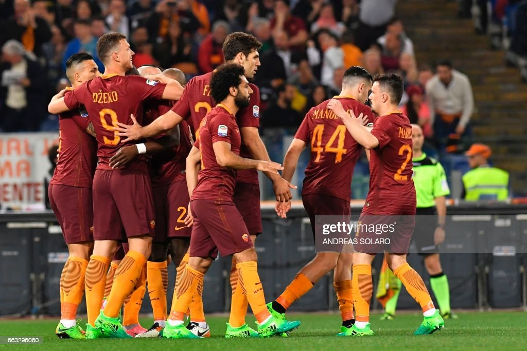 AS Roma's forward From Bosnia Edin Dzeko (L) celebrates with his teammates after scoring during the Italian Serie A football match AS Roma vs Empoli on April 1, 2017 at Rome's Olympic stadium. /