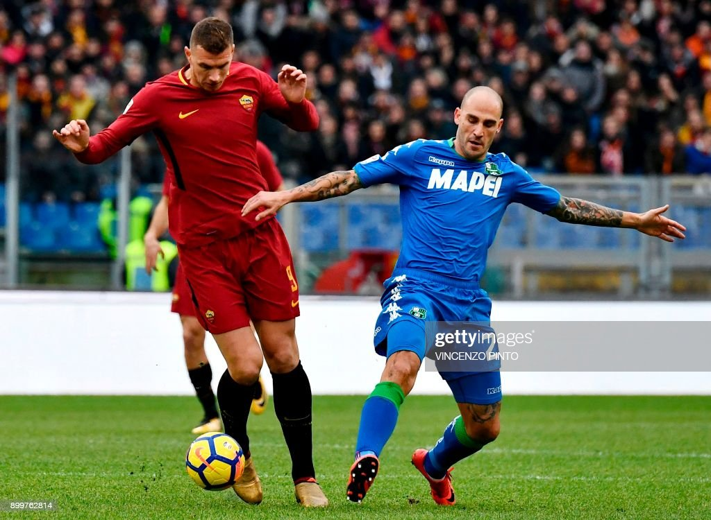 AS Roma's forward from Bosnia Edin Dzeko (L) vies with Sassuolo's defender from Italy Paolo Cannavaro during the Italian Serie A football match AS Roma vs Sassuolo on December 30, 2017 at the Olympic stadium in Rome. / AFP PHOTO / Vincenzo PINTO