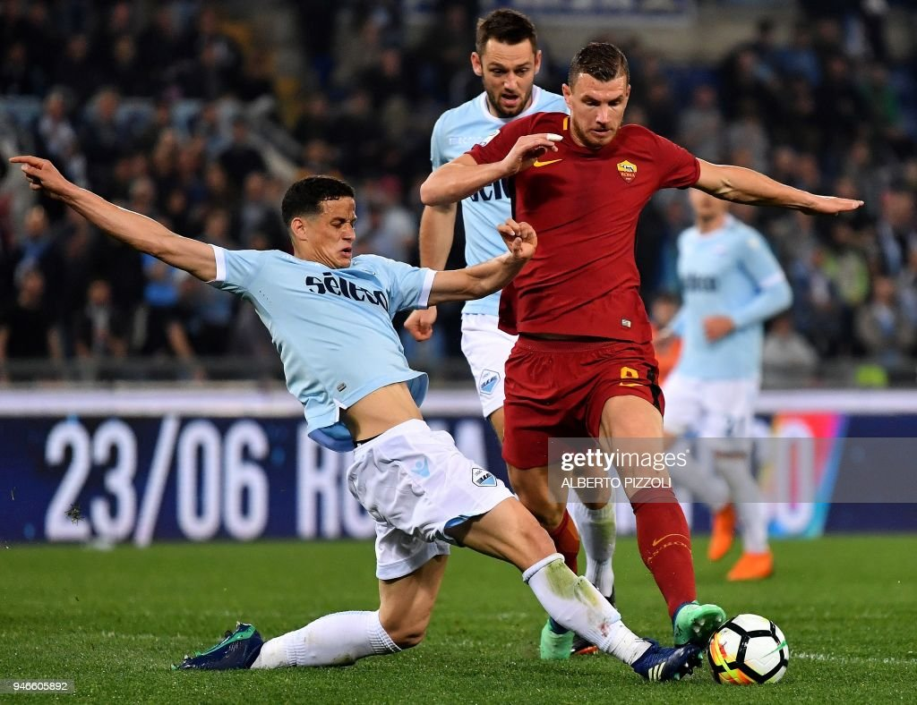 Roma's forward from Bosnia Herzegovina Edin Dzeko (R) vies for the ball with Lazio's defender from Netherlands Wesley Hoedt (L) during the Italian Serie A football match between Lazio and Roma on April 15, 2018 at Olympic Stadium in Rome. /