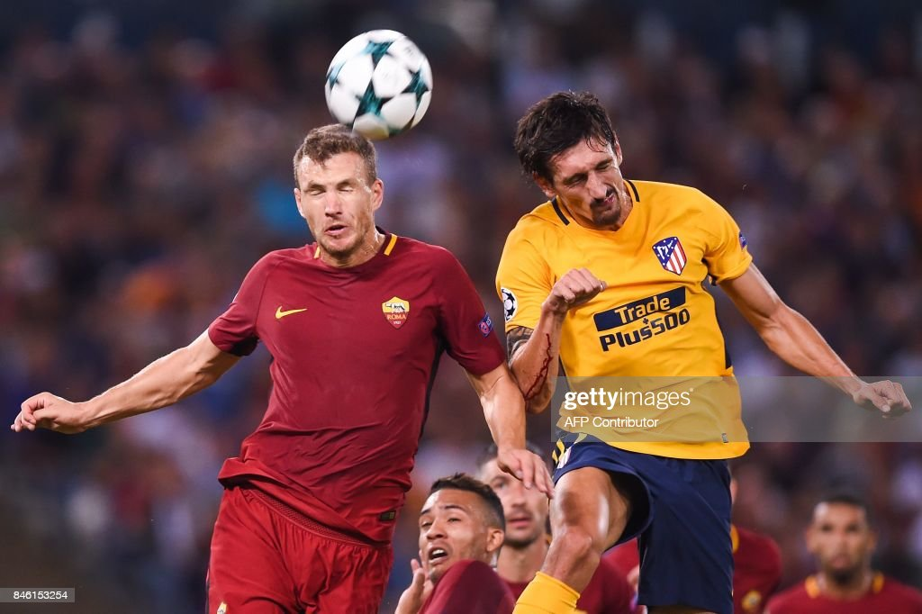 Roma's forward from Bosnia-Herzegovina Edin Dzeko (L) and Atletico Madrid's defender from Montenegro Stefan Savic go for a header during the UEFA Champions League Group C football match between AS Roma and Atletico Madrid on September 12, 2017 at the Olympic stadium in Rome. / AFP PHOTO / Filippo MONTEFORTE