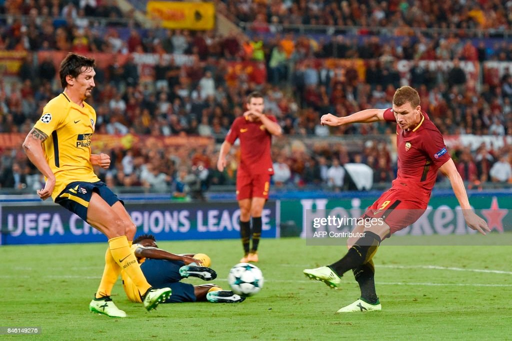 Roma's forward from Bosnia-Herzegovina Edin Dzeko (R) shoots on goal during the UEFA Champions League Group C football match between AS Roma and Atletico Madrid on September 12, 2017 at the Olympic stadium in Rome. / AFP PHOTO / Andreas SOLARO