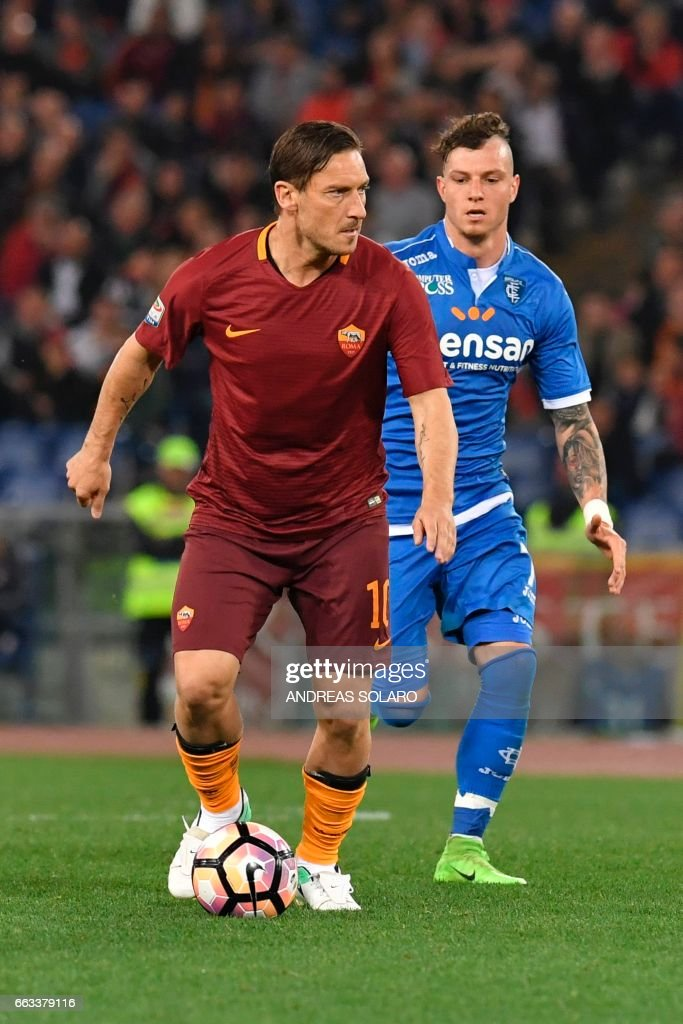 AS Roma's forward from Italy Francesco Totti (L) controls the ball next to Empoli's defender from Austria Marcel Buchel during the Italian Serie A football match AS Roma versus Empoli on April 1, 2017 at Olympic stadium in Rome. /