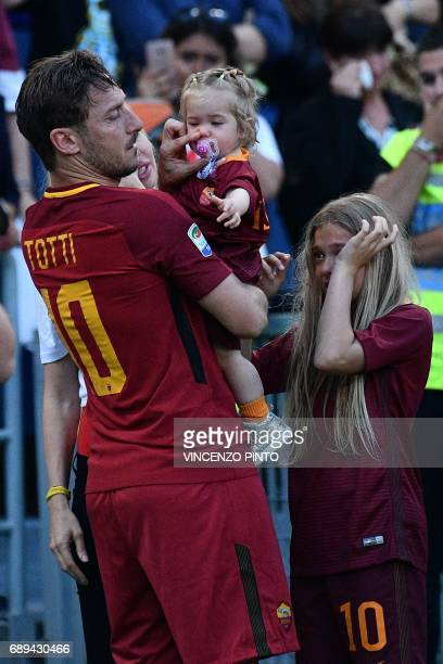 Roma's forward from Italy Francesco Totti holds his daughter Isabel as his other daughter Chanel Totti cries during a ceremony to celebrate his last...