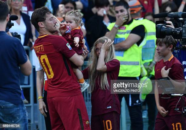 Roma's forward from Italy Francesco Totti holds his daughter Isabel as his other children Chanel and Cristian cry during a ceremony to celebrate his...