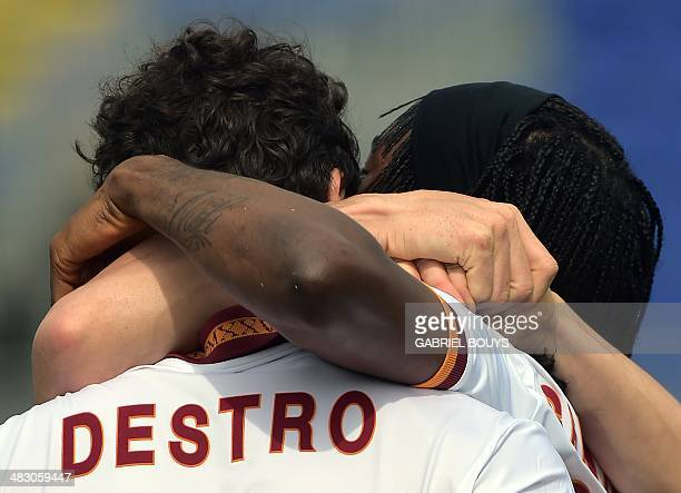 AS Roma's forward Mattia Destro is congratulated by teammate Gervinho after scoring a goal during the Italian Serie A football match between Cagliari...
