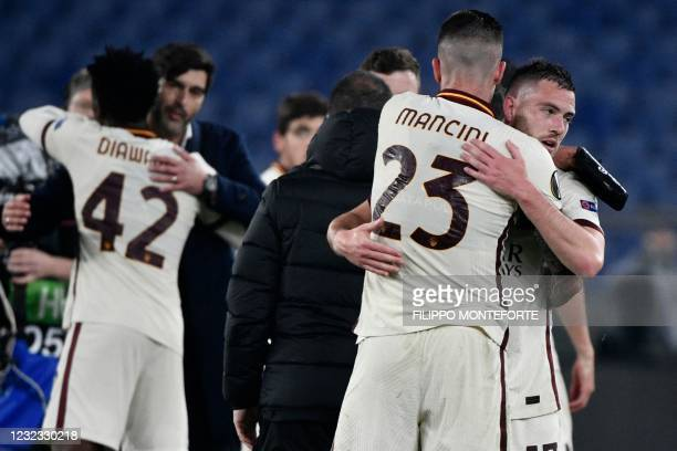Roma's French midfielder Jordan Veretout and Roma's Italian defender Gianluca Mancini embrace at the end of the UEFA Europa League quarter final...