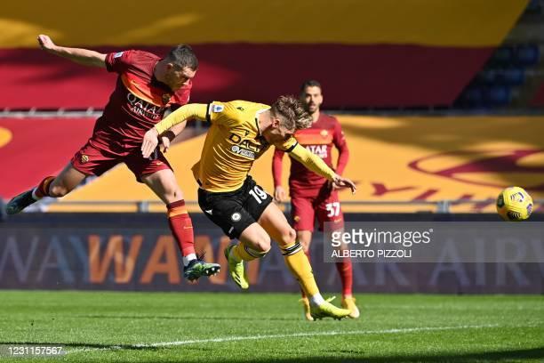 Roma's French midfielder Jordan Veretout scores a header despite Udinese's Danish defender Jens Stryger Larsen to open the scoring during the Italian...