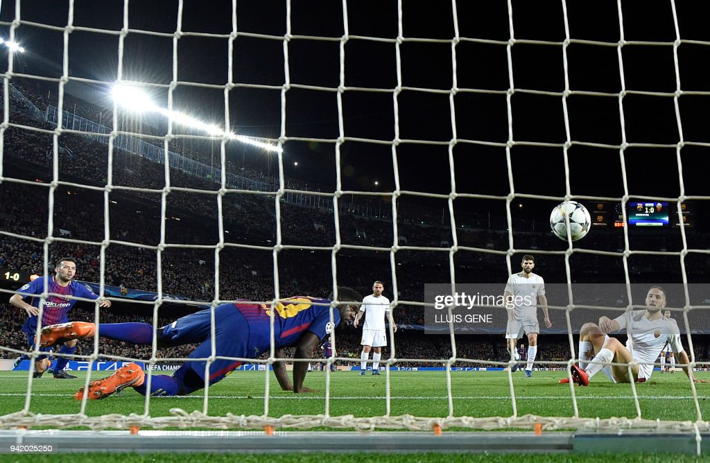 Roma's Greek defender Kostas Manolas (R) scores an own-goal beside Barcelona's French defender Samuel Umtiti (2L) during the UEFA Champions League quarter-final first leg football match between FC Barcelona and AS Roma at the Camp Nou Stadium in Barcelona on April 4, 2018. /