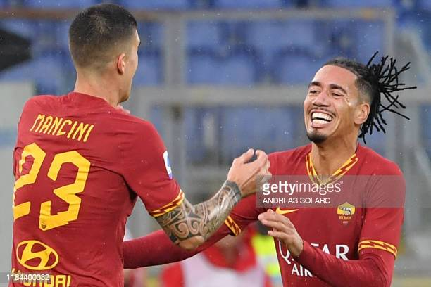 AS Roma's Italian defender Gianluca Mancini celebrates with AS Roma's English defender Chris Smalling after scoring his team's second goal during the...
